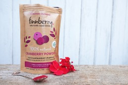 A photo of the finnberry cranberry pack, next to spoon and flowers